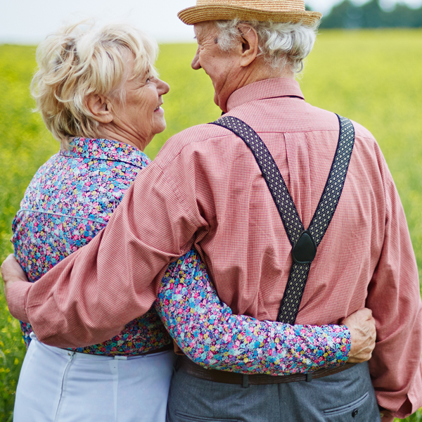 Old couple arms around each other smiling in feild