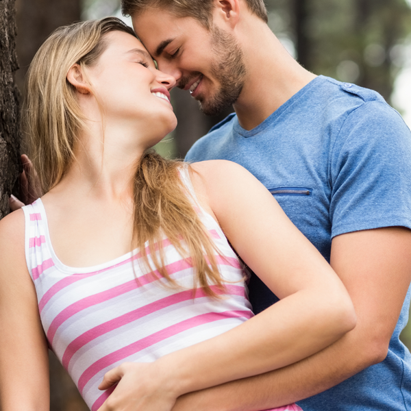 Couple outdoors against tree cuddling eyes closed head to head