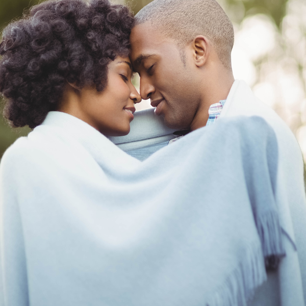 black couple outside head to head blanket eyes closed