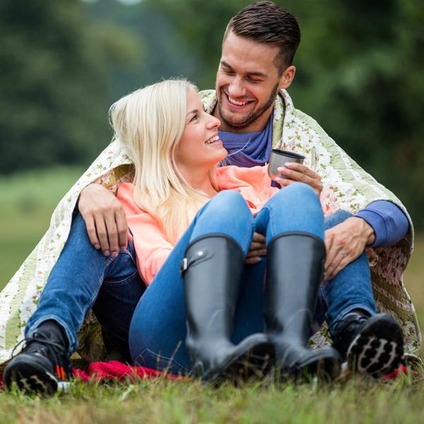 couple outside smiling cuddling summer blanket