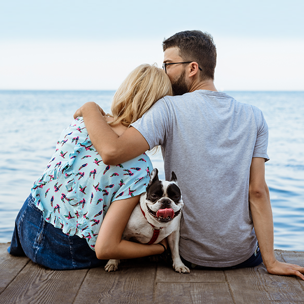 couple-outdoors-man-kissing-womans-head-backs-dog-hugging-side-facing-ocean-sitting-on-doc